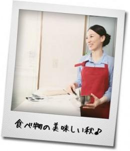 笑顔で調理をしてるエプロン姿の女性の写真