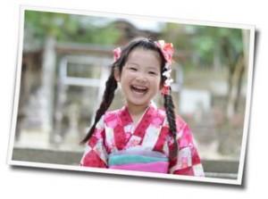 浴衣を着てカメラに笑顔を向ける女の子の写真